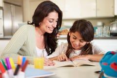 有读书家庭作业的母亲帮助的女儿在表上 免版税库存图片