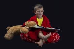 有读书的玩具熊的滑稽的男孩在床时间前 免版税库存照片