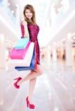 有购买的微笑的妇女在购物中心 免版税库存照片