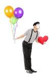 有给亲吻的气球和红色心脏的年轻笑剧艺术家 免版税库存照片