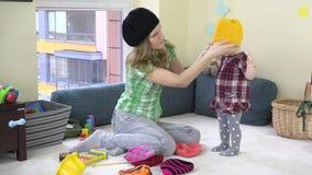 有令人敬畏的女婴措施五颜六色的被编织的帽子的母亲在玩具之间 股票视频