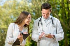 有年轻人的年轻医生和俏丽的助理 免版税库存图片