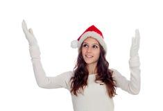有延伸她的胳膊的圣诞节帽子的可爱的偶然女孩 免版税库存图片