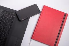 有黑便携式计算机、巧妙的电话和笔记本的工作场所在白色背景 库存图片