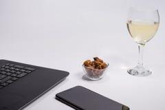 有黑便携式计算机、巧妙的电话,干葡萄和玻璃白葡萄酒的工作场所在白色背景 库存图片