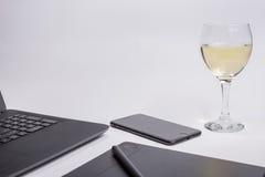 有黑便携式计算机、数字式图形输入板和笔巧妙的电话和玻璃白葡萄酒的工作场所在白色背景 免版税库存照片