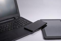 有黑便携式计算机、片剂计算机和巧妙的电话的工作场所在白色背景 免版税库存图片