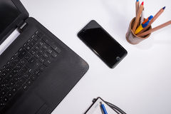 有黑便携式计算机的工作场所、巧妙的电话、笔记本和笔和箱子有颜色笔和铅笔的在白色背景 库存图片