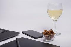 有黑便携式计算机的工作场所、数字式图形输入板和笔、巧妙的电话,干葡萄和玻璃白葡萄酒在白色backgr 免版税库存照片