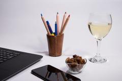 有黑便携式计算机的工作场所,巧妙的电话、箱子有颜色笔的和铅笔烘干葡萄和玻璃白葡萄酒在白色backgr 免版税库存图片