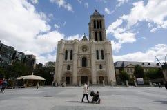 有婴儿推车的妇女由圣但尼大教堂走 免版税库存图片