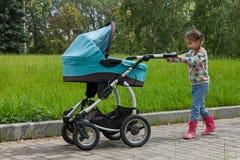 有婴儿推车的小女孩 免版税库存照片