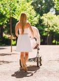 有婴儿推车的愉快的母亲在公园 库存照片