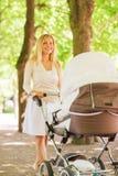 有婴儿推车的愉快的母亲在公园 图库摄影