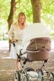 有婴儿推车的愉快的母亲在公园 免版税库存图片