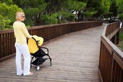 有婴儿推车的年轻母亲在公园 库存图片
