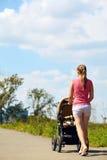 有婴儿推车的年轻母亲 免版税库存图片
