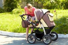 有婴儿推车的年轻母亲 免版税库存照片