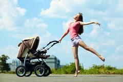 有婴儿推车的年轻母亲 免版税图库摄影