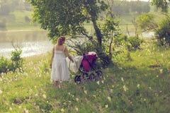 有婴儿车的一名妇女在森林里走 免版税库存图片