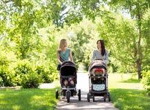 有婴儿车的母亲走在公园的 库存图片