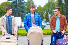 有婴儿车的年轻父亲在城市走 免版税库存照片