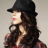 有经典帽子的美丽的深色的女孩 库存照片