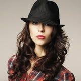有经典帽子的美丽的深色的女孩 免版税库存照片
