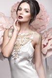 有经典构成和发型的美丽的女孩在有大花的精美内衣在背景 秀丽表面 库存图片