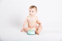 有结冰的婴孩在他的坐在蛋糕旁边的嘴 库存图片
