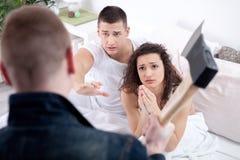 有柴刀的恼怒的丈夫捉住了有恋人的欺诈的妻子 免版税库存图片