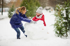 有更加年轻的入学年龄修造的女儿的母亲一个雪人在公园 库存图片