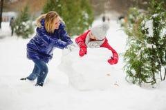 有更加年轻的入学年龄修造的女儿的母亲一个雪人在公园 免版税库存图片