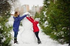 有更加年轻的入学年龄修造的女儿的母亲一个雪人在公园 库存照片