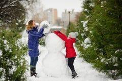 有更加年轻的入学年龄修造的女儿的母亲一个雪人在公园 免版税图库摄影