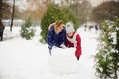 有更加年轻的入学年龄修造的女儿的母亲一个雪人在公园 免版税库存照片