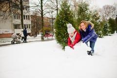 有更加年轻的入学年龄修造的女儿的母亲一个雪人在围场 库存照片