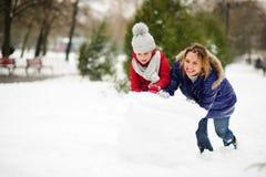 有更加年轻的入学年龄修造的女儿的母亲一个雪人在围场 库存图片