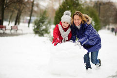 有更加年轻的入学年龄修造的女儿的母亲一个雪人在围场 免版税库存图片