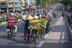 有移动在路的街道的棕榈叶圆锥形帽子的典型的街道果子供营商 免版税库存照片