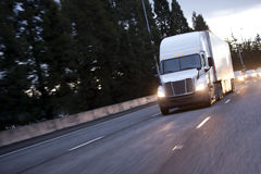 有移动由宽上流的拖车的现代白色大半船具卡车 免版税库存照片