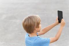 有移动电话的男孩 拍与他的智能手机的孩子照片 灰色都市背景 回到视图 概念查出的技术白色 库存照片