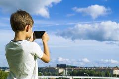 有移动电话的男孩 采取照片他的智能手机的孩子 美好的天空和城市背景 回到视图 技术 库存图片