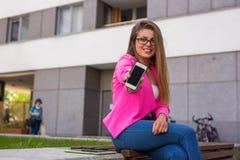有移动电话的年轻美丽的女实业家在工作以后 图库摄影
