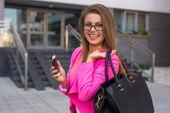有移动电话的年轻美丽的女实业家在工作以后 免版税库存图片