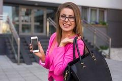 有移动电话的年轻美丽的女实业家在工作以后 免版税图库摄影