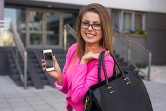 有移动电话的年轻美丽的女实业家在工作以后 库存图片