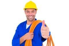 有滚动的导线的电工打手势赞许的 免版税库存照片