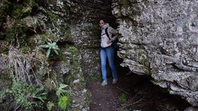 有移动通过岩石或出去从洞的背包的小姐远足者 影视素材