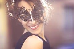 有黑化妆舞会面具的愉快的少妇 免版税库存图片